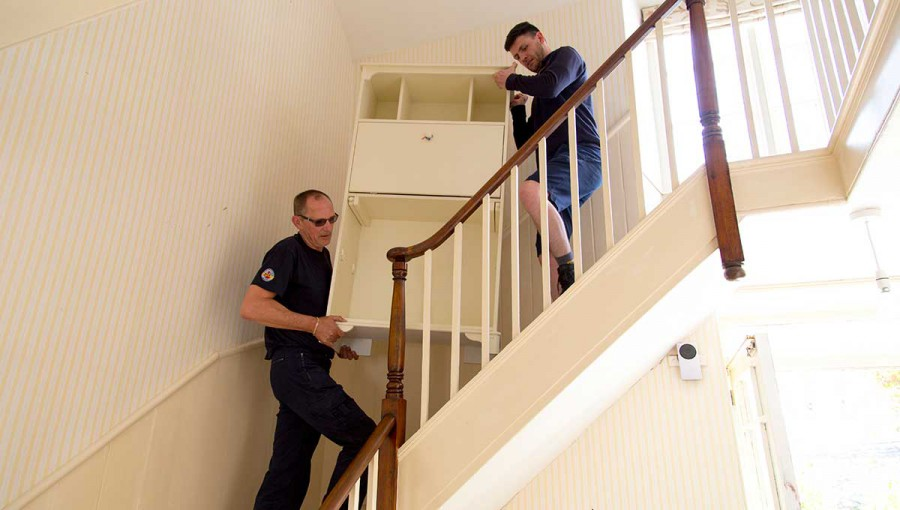 Tripp removals staff lift dresser on stairs