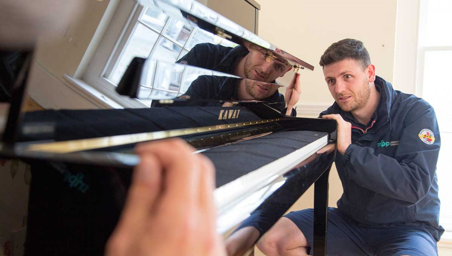 Tripp removals staff slide piano into place