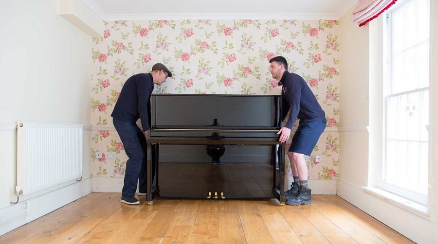 Tripp removals staff lift piano into place