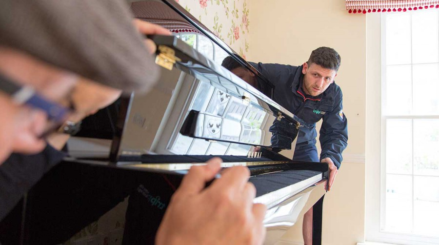 Tripp removals carefully lifting piano